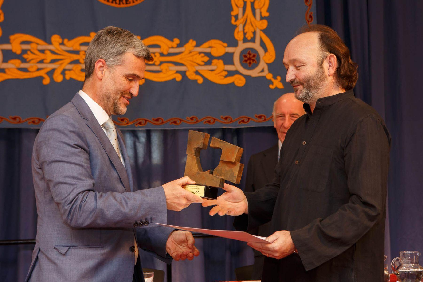 Moncho Ferrer recoge el Premio Internacional Jaime Brunet a la Promoción de los Derechos Humanos de manos del rector de la UPNA, Alfonso Carlosena.