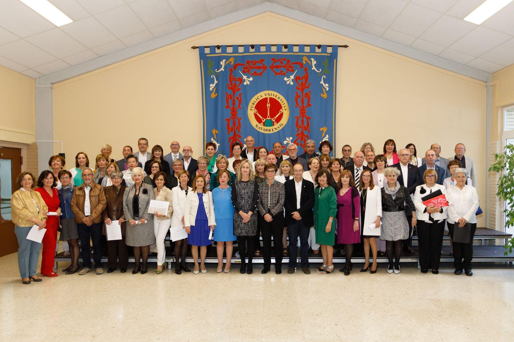 Estudiantes del Aula de la Experiencia pertenecientes a la XIII Promoción de Pamplona posan con las autoridades tras concluir su graduación.