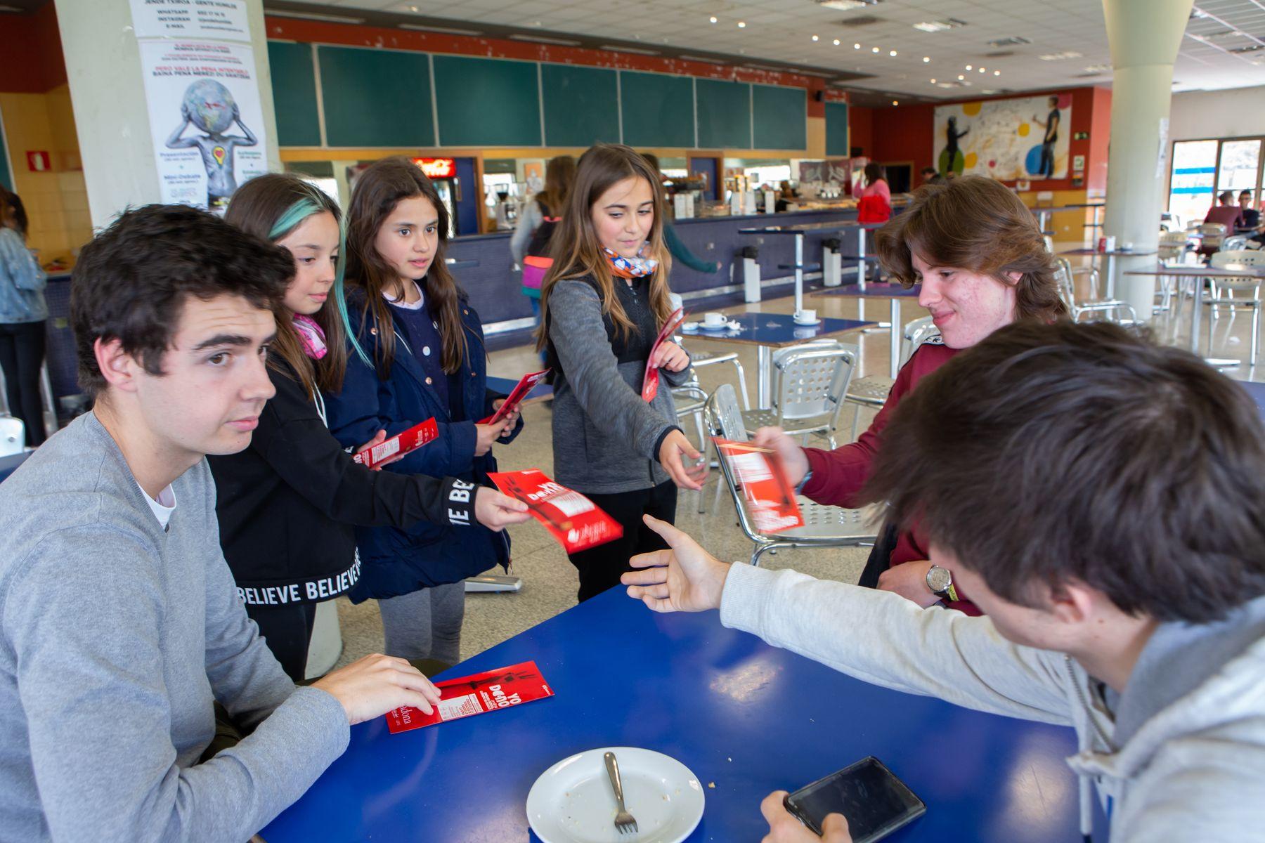 Estudiantes de Primaria entregan un folleto sobre donación de sangre a alumnos universitarios en una de las cafeterías del campus de Arrosadia.