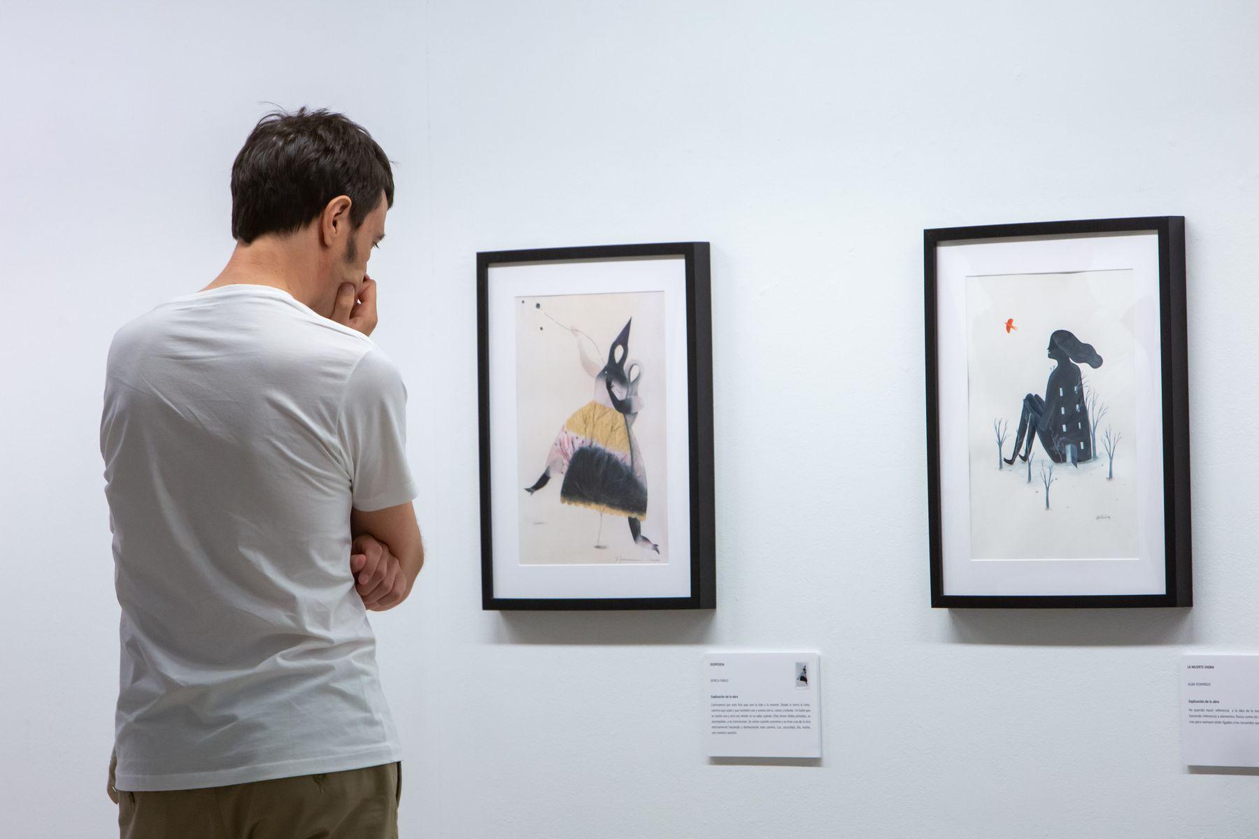 Una persona observa las imágenes de la exposición.