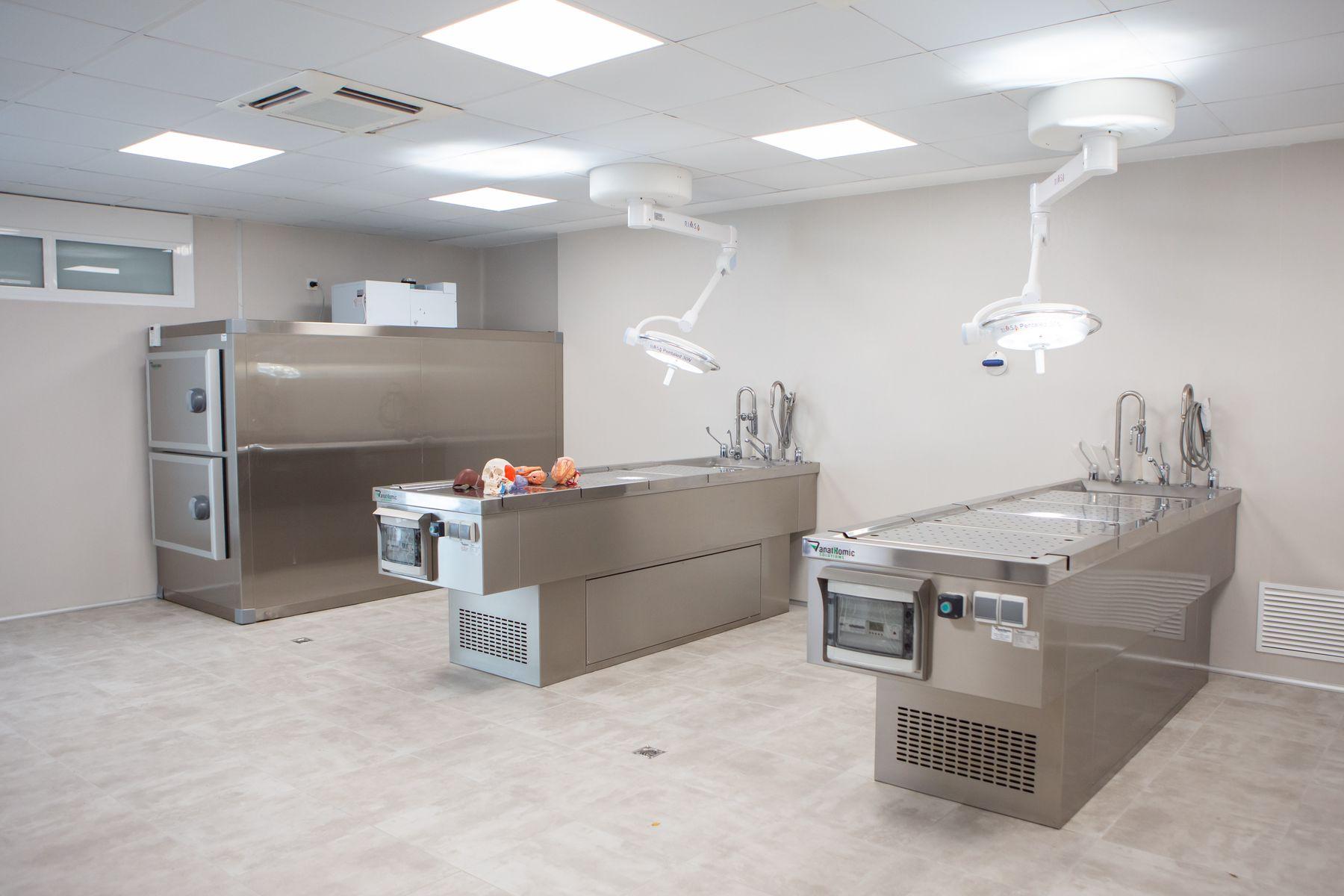 Vista general de la sala de disección de cadáveres con cámaras frigoríficas, mesas de tanatopraxia y lavamanos.
